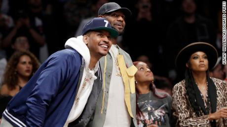 Carmelo Anthony, left, and LeBron James watch Dwyane Wade play in his last NBA game on April 10, 2019, in New York with Gabrielle Union, right.