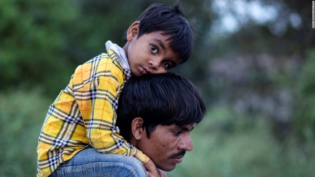 A migrant worker carries a child as they walk along a road in New Delhi.