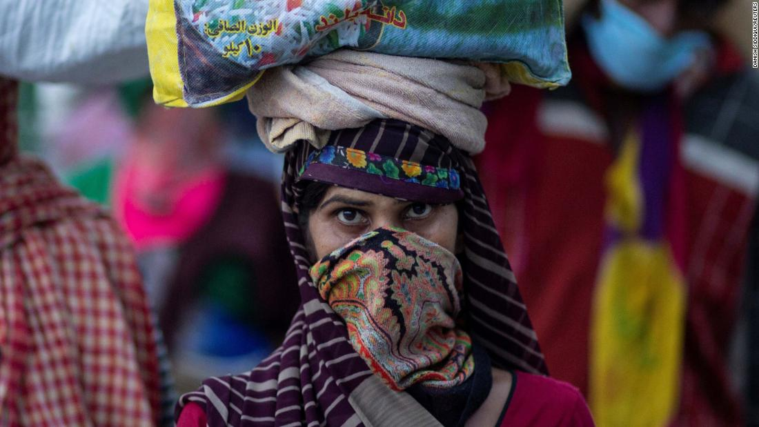 A migrant worker carries her belongings along a roadside in New Delhi.