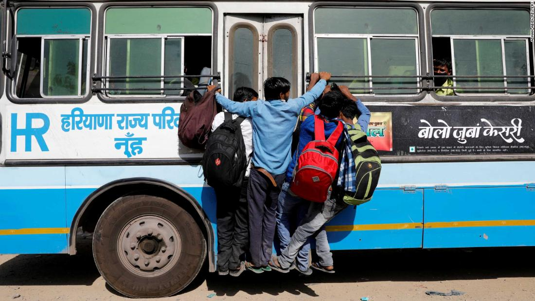People hang on to a door of a moving bus on the outskirts of New Delhi.