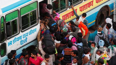 Migrant workers try to board a crowded bus as they return to their villages, during a 21-day nationwide lockdown to limit the spreading of coronavirus disease (COVID-19), in Ghaziabad, on the outskirts of New Delhi, India, March 29, 2020. REUTERS/Adnan Abidi