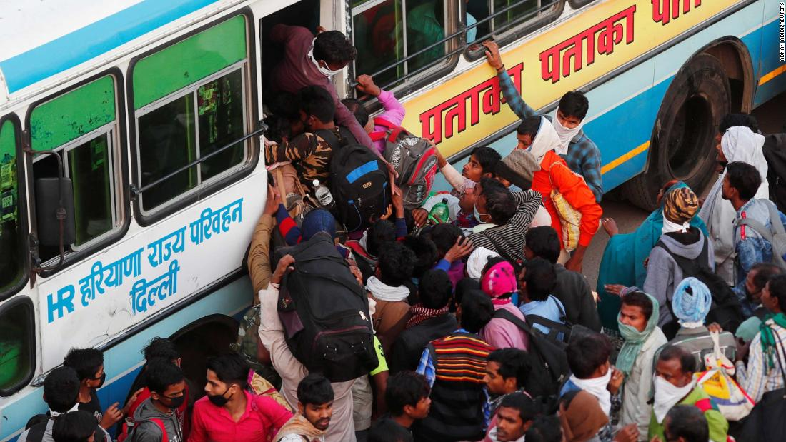 Migrant workers try to board a crowded bus in Ghaziabad on Sunday, March 29. The state governments of Uttar Pradesh, Bihar and Haryana arranged for hundreds of buses to ferry migrants home, causing chaotic scenes as thousands descended upon stations trying to claw their way onto buses.