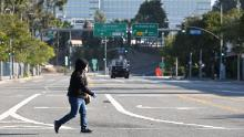 A woman wears a mask as she crosses an empty street near the Los Angeles Convention Center.