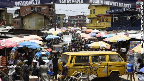 People walk in a crowded market in defiance to a social spacing order, to make last minute shopping ahead of a curfew, at the Mushin Market in Lagos, on March 30, 2020.