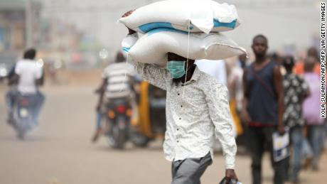 "A man carries bags of rice on his head at a border between Abuja and the Nasarawa State on March 30, 2020, as he leaves to neighbouring states after Nigeria's President Muhammadu Buhari called for a lockdown to limit the spread of the COVID-19 coronavirus. - Over 20 million Nigerians on Monday scrambled to prepare for lockdown in sub-Saharan Africa's biggest city Lagos and the capital Abuja, as the continent struggled to curb the spread of the COVID-19  coronavirus. President Muhammadu Buhari has ordered a two-week ""cessation of all movements"" in the key cities from 2200 GMT in a bid to ward off an explosion of cases in Africa's most populous country. (Photo by Kola SULAIMON / AFP) (Photo by KOLA SULAIMON/AFP via Getty Images)"
