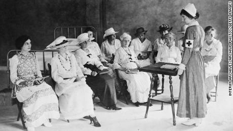 An unidentified Red Cross nurse teaches a class on home hygiene and care for the sick to a group of women of various ages, 1920.