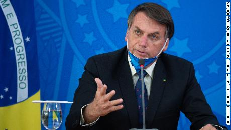 President Jair Bolsonaro takes off his protective mask to speak to journalists in Brasilia during a March news conference about the coronavirus outbreak.