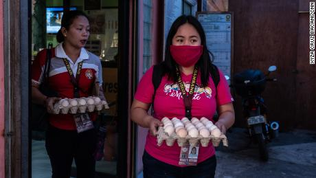 Rosalie Natividad wears a makeshift mask as she carries eggs to local families.