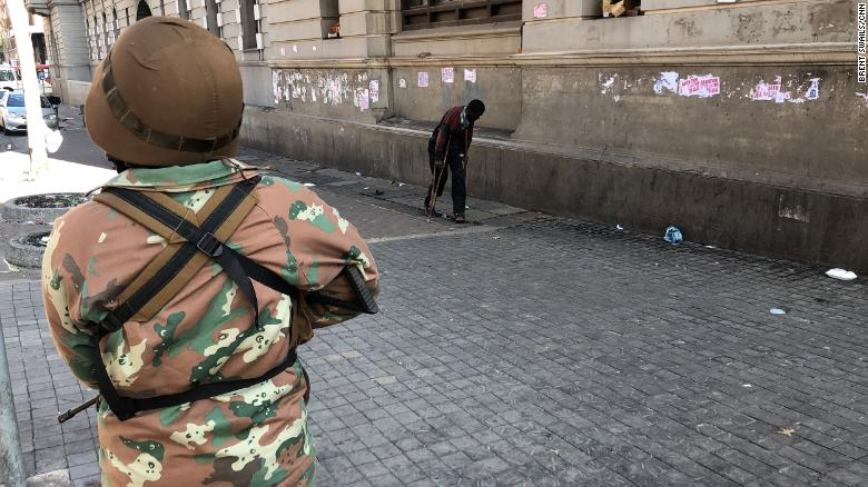 A soldier looks on past a man on crutches during South Africa's lockdown.