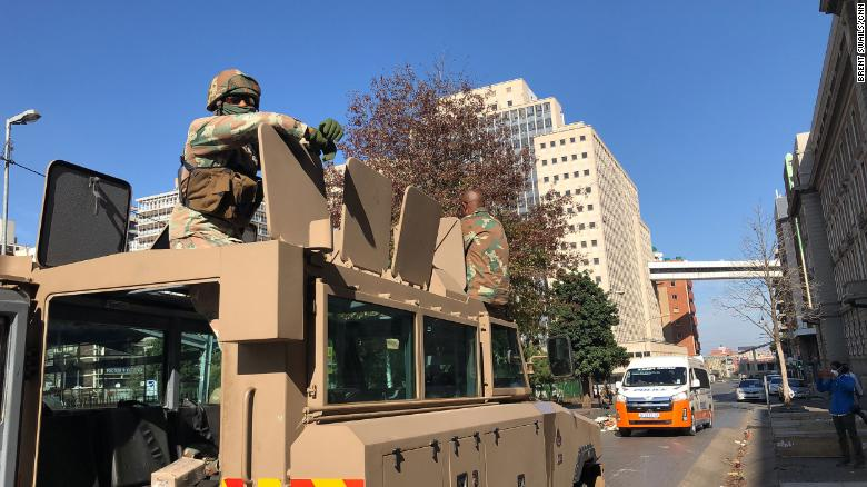 Two South African soldiers sit on top of their armored personnel carrier in Johannesburg city center.