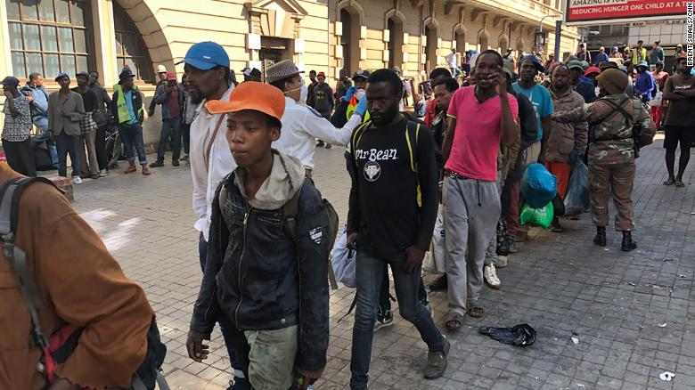 Lines of homeless South Africans await police transport to temporary shelters in downtown Johannesburg.