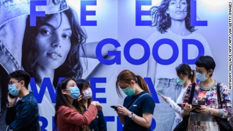 Pedestrians wear face masks as a precautionary measure as they wait for a bus in Hong Kong on March 23, 2020, after the citys Chief Executive announced plans to temporarily ban the sale of alcohol in bars and restaurants as a measure to help stop the spread of the COVID-19 caused by the novel coronavirus. - Hong Kong will ban all non-residents from entering the city from midnight on March 24, 2020 in a bid to halt the coronavirus, its leader says, as she unveils plans to stop restaurants and bars serving alcohol. (Photo by ANTHONY WALLACE / AFP) (Photo by ANTHONY WALLACE/AFP via Getty Images)
