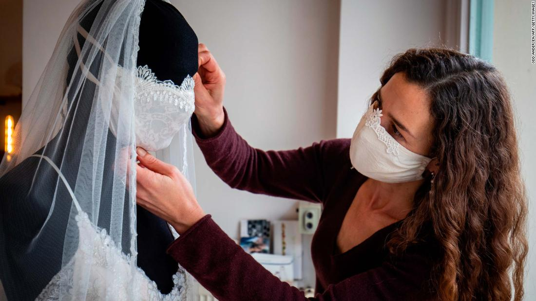 Designer Friederike Jorzig adjusts a mannequin wearing a wedding dress and a face mask at her store in Berlin on March 31, 2020.