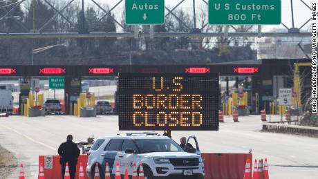 US Customs officers stand beside a sign saying that the US border is closed at the US/Canada border in Lansdowne, Ontario, on March 22, 2020. - The United States agreed with Mexico and Canada to restrict non-essential travel because of the coronavirus, COVID-19, outbreak and is planning to repatriate undocumented immigrants arriving from those countries. (Photo by Lars Hagberg / AFP) (Photo by LARS HAGBERG/AFP via Getty Images)