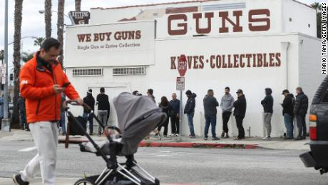 A man walks with a stroller as people stand in line outside the Martin B. Retting, Inc. guns store on March 15, in Culver City, California. The FBI has seen a spike in gun sale background checks amid the coronavirus pandemic.