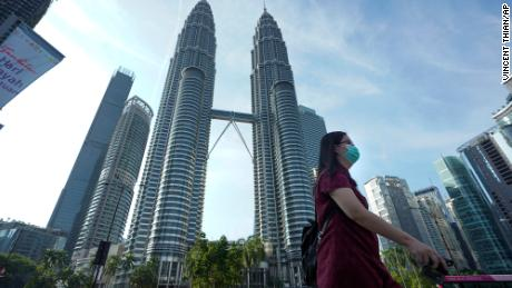 A woman wearing a face mask walks in front of Twin Towers in Kuala Lumpur, Malaysia, on March 18.