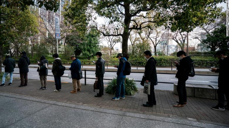 Commuters wait in line at a bus stop on March 26, 2020 in Tokyo, Japan.