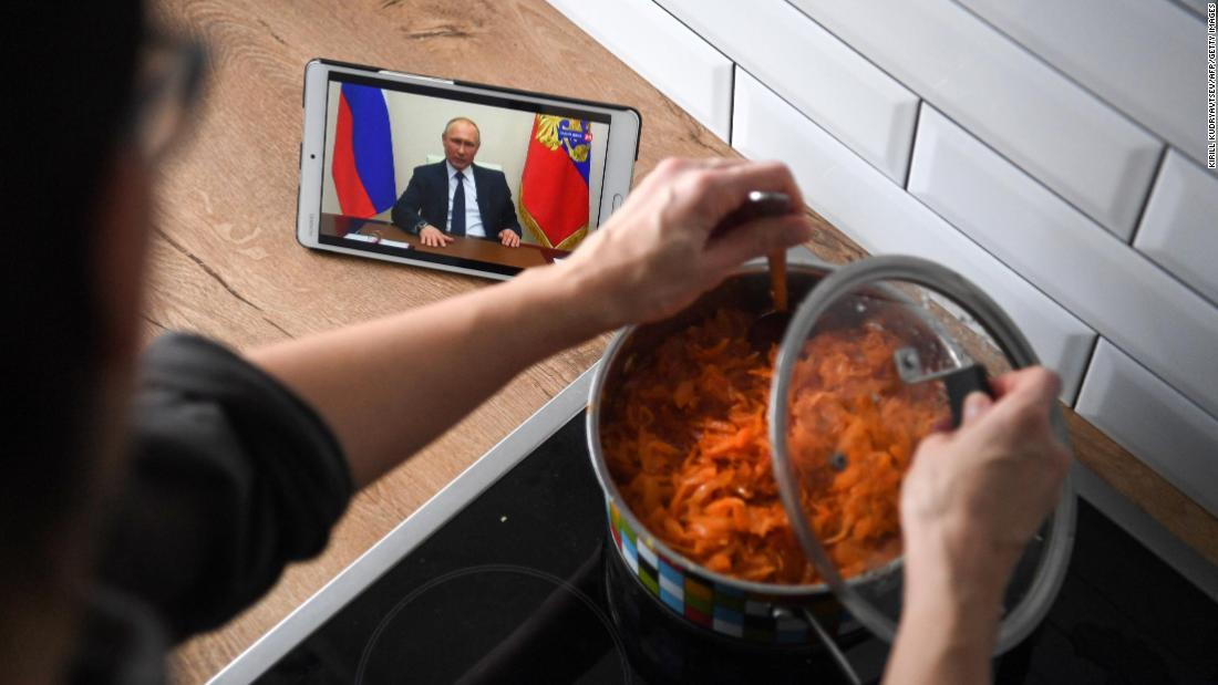 A woman in Moscow cooks while watching Russian President Vladimir Putin address the nation over the coronavirus pandemic.