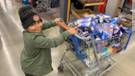 Cavanaugh Bell, 7, shops for items to make care packages for the elderly.