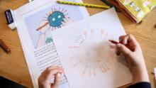 A child draws a COVID-19 coronavirus as part of school homeworks.