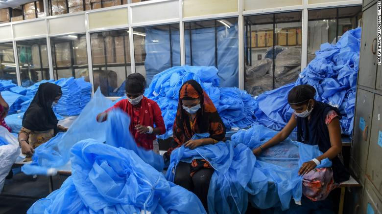 Workers prepare protective clothing and gear at a facility of personal protective equipments manufacturer Nikshe Multiproducts on the outskirts of Ahmedabad on April 2, 2020.