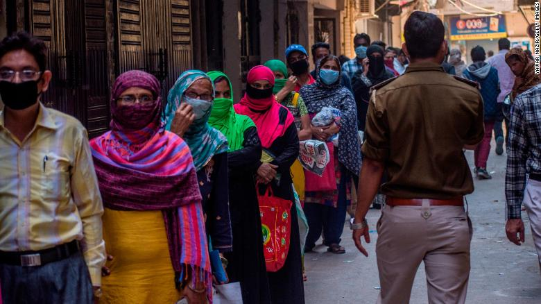 Indians wait to receive rations during the nationwide lockdown on April 2, 2020 in New Delhi.