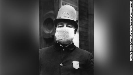 "An American policeman wearing a ""flu mask"" to protect himself from the outbreak of Spanish Flu following World War I."