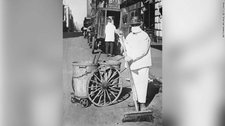 Un addetto alle pulizie di New York che indossa una maschera per controllare la diffusione dell'epidemia di influenza.  & quot; Meglio essere ridicoli che morti, & quot;  è l'opinione di un funzionario.
