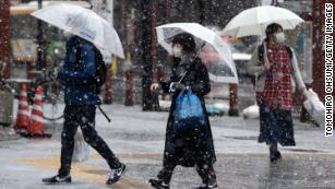 Snow falls as people wearing face masks walk through Tokyo's  Asakusa district on March 29.