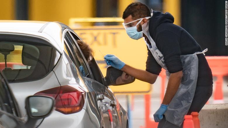 """Медицински персонал работи в Националния център за изпитване на coronavirus Националната здравна служба на паркинга ИКЕА на """"Уембли"""", Лондон."""