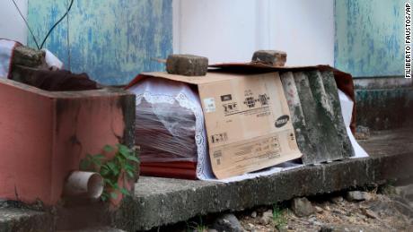 Un sicriu care conține trupul unei persoane care a murit de Covid-19 se află învelit în plastic și acoperit cu carton, în afara unui bloc de apartamente familiale din Guayaquil, pe 2 aprilie.