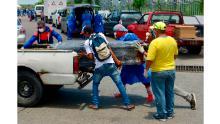 Bărbații care au echipament de protecție încarcă un sicriu într-o mașină din fața unui spital din Guayaquil.