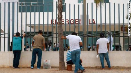 Rudele așteaptă în afara unui spital pentru informații despre membrii familiei infectate cu Covid-19 în Guayaquil pe 1 aprilie.