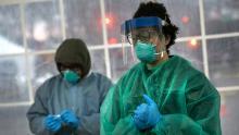 Un medico SOMOS Community Care si prepara a valutare un paziente presso un centro di test di screening del coronavirus.