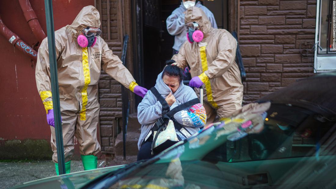 A woman suspected of having coronavirus is helped from her home by emergency medical technicians Robert Sabia, left, and Mike Pareja, in Paterson, New Jersey, on March 24.