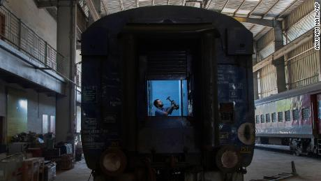 An Indian railroad worker is working to convert a train wagon into an isolation station for the fight against the new coronavirus in Gauhati, India, on Sunday March 29, 2020.