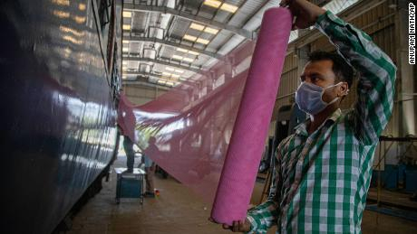 Indian railroad workers repair mosquito nets while they are working to convert a train wagon into an isolation station for the fight against the new coronavirus in Guwahati, India, on Sunday March 29, 2020.