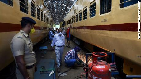 Workers wearing face masks work on March 30, 2020 in a bus factory workshop in Chennai on railroad cars that serve as temporary isolation stations to prepare for Covid-19 coronavirus patients.