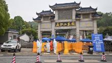 People wearing hazmat suits standing guard at the entrance to the Biandanshan cemetery in Wuhan on March 31.