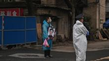 A man wearing a mask and a blue raincoat holds a portrait as he stands outside the Biandanshan cemetery in Wuhan on March 31.