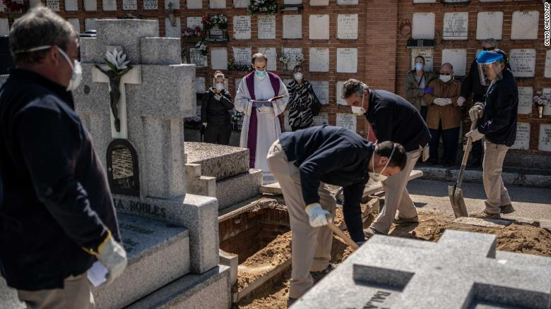 A priest and relatives pray as a victim is buried at the cemetery on March 28.