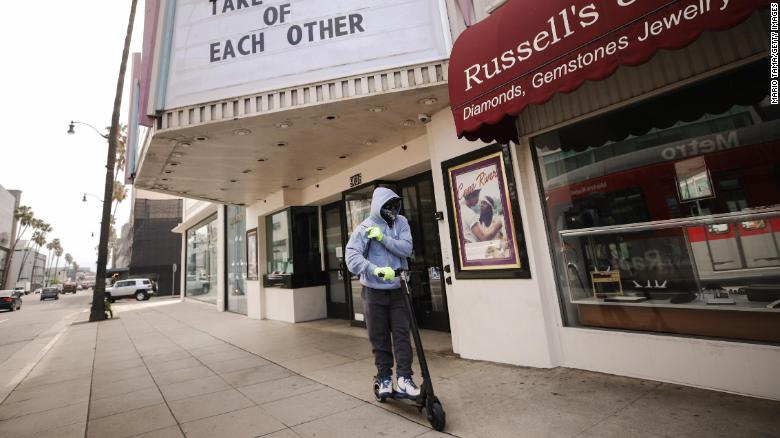 A man wears gloves and a bandanna across his face while riding a scooter on March 18, 2020 in Beverly Hills, California.