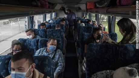 Venezuelan migrants wear protective masks while sitting on a bus that will return them back to Venezuela, in Bogota, Colombia, on Sunday, April 5, 2020.