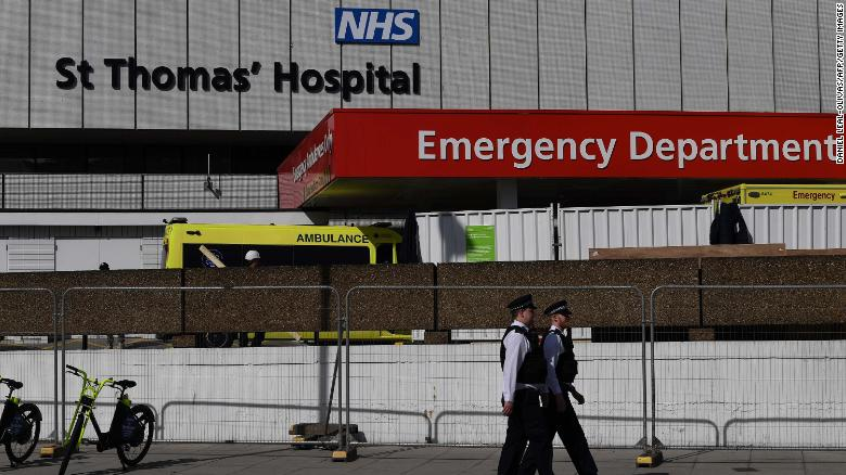 British police officers stand on duty outside St Thomas' Hospital in central London, where Britain's Prime Minister Boris Johnson is in intensive care on April 7, 2020.