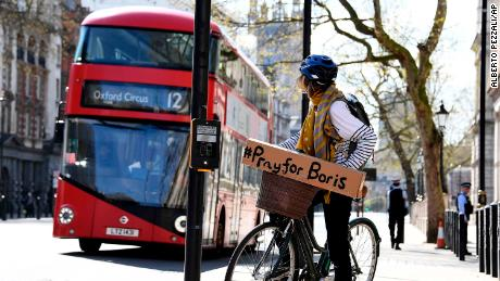 A woman with a sign of support on her bicycle in London as leaders from across the world expressed their hope that Johnson would make a rapid recovery.