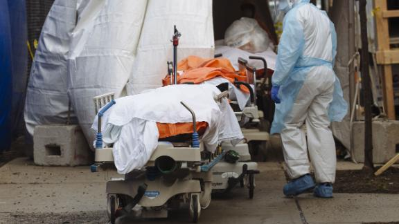 A medical worker in protective clothing walks past the bodies of deceased patients from a refrigerated overflow morgue outside the Wyckoff Heights Medical Center in Brooklyn, New York, U.S., on Friday, April 3, 2020. Officials from New York City began to warn that the health system was nearing its capacity to handle the waves of patients, with possibly just days to go before reaching the limits of ventilators and hospital bed space. Photographer: Angus Mordant/Bloomberg via Getty Images