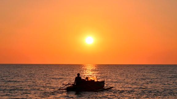 This photo taken on February 14, 2020 shows a Filipino fisherman sailing off at sunset from the coast of Bacnotan, La Union province, in northwestern Philippines facing the South China Sea. (Photo by Romeo GACAD / AFP) (Photo by ROMEO GACAD/AFP via Getty Images)