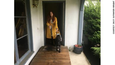 Sassy Outwater-Wright leaves her home with her guide dog.