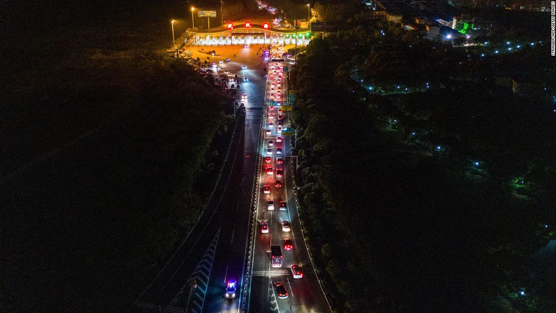 Cars in Wuhan line up to leave at a highway toll station.