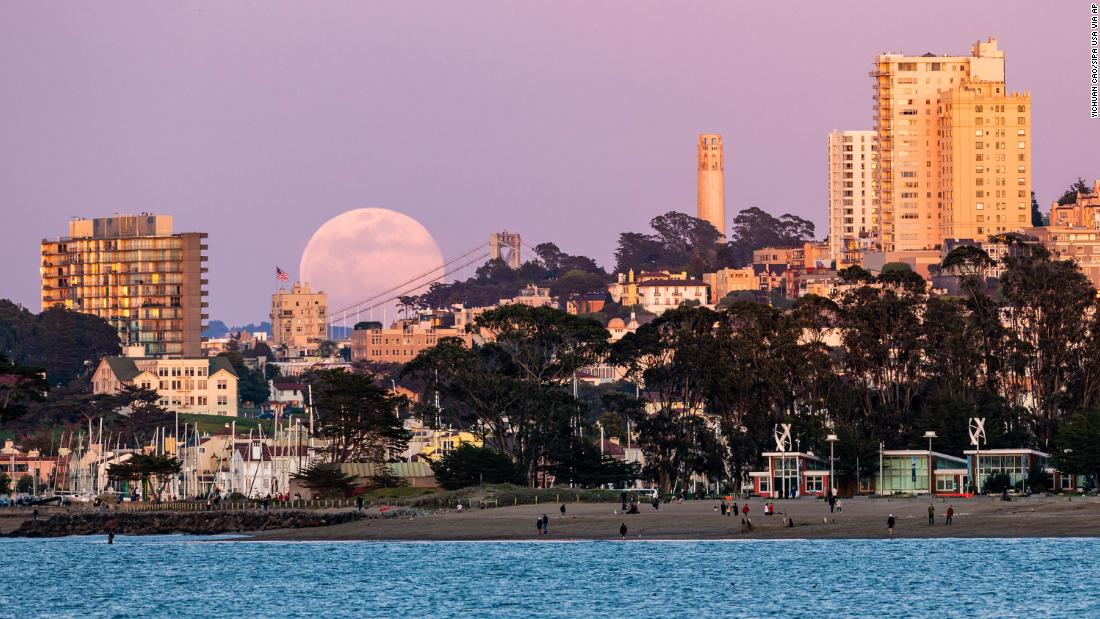 The full moon rises above the horizon in San Francisco, California.